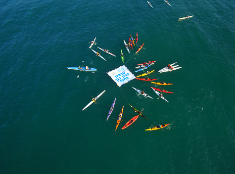 Kayaks circling a sign in the deep sea